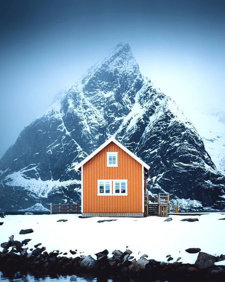 Lonely house in front of a lonely mountain Snow Winter Cold Temperature Built Structure Architecture Building Exterior House Building Sky Nature No People Day Covering Hut Mountain Snowcapped Mountain Frozen Wood - Material Outdoors Cottage