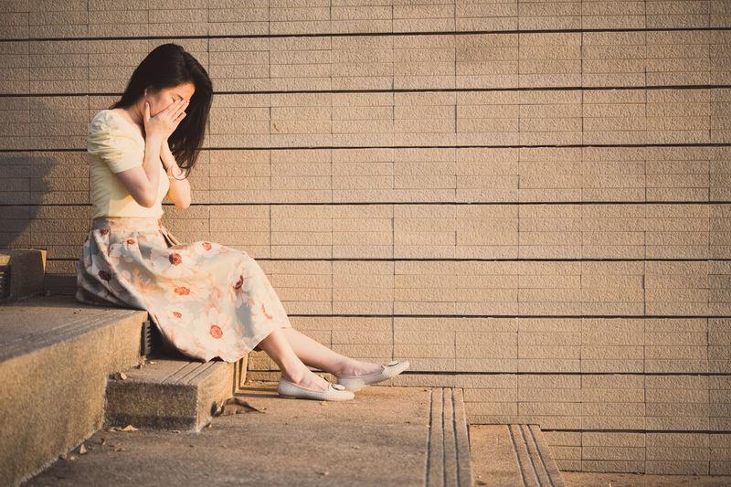 Sad woman sitting on steps against wall