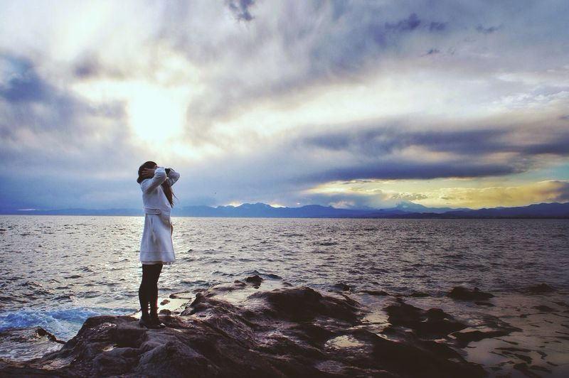 Rear view of man standing on beach against cloudy sky