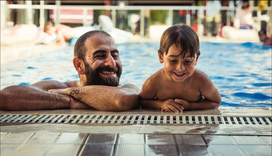 Father and son EyeEm Selects Swimming Pool Pool Two People Water Leisure Activity Men Lifestyles Real People People Emotion Smiling Happiness Young Men Mature Men Outdoors Day Focus On Foreground Shirtless Adult Males  A New Perspective On Life