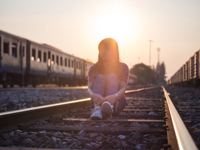 Woman sitting on railroad track against sky during sunset