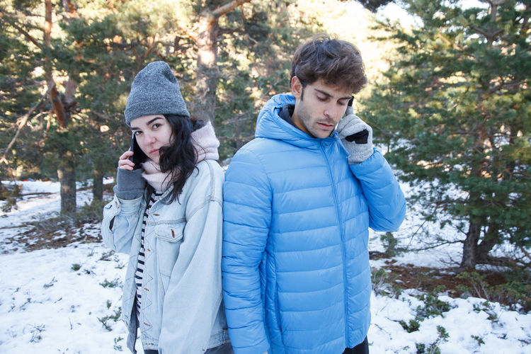 Boyfriend and girlfriend couple are talking on the phone while they are on a date in the mountains on a snowy day. Angry Couple Date Love Relationship Self Selfishness Trip Unhappy Anger Boyfriend Chat Cold Communication Connection Egocentrism Girlfriend Phone Smart Phone Snow Talking Technology Togetherness Two People Winter