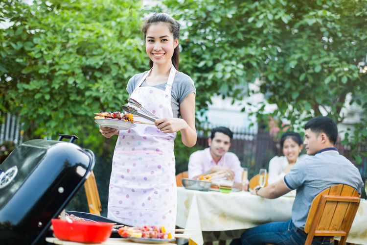 Adult Barbecue Cheerful Emotion Enjoyment Food Food And Drink Group Of People Hair Happiness Holding Leisure Activity Lifestyles Looking At Camera Meal Portrait Preparation  Smiling Three Quarter Length Toothy Smile Women Young Adult Young Women