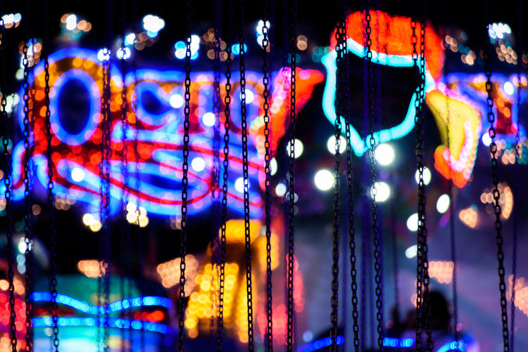 Close up of chains of a chairoplane with neon lights in the background Carousel Chains Chairoplane Fair First Eyeem Photo Funfair Hanging Illuminated Light Multi Colored Neon Neon Lights Night Nightlife Nightphotography Outdoors Selective Focus