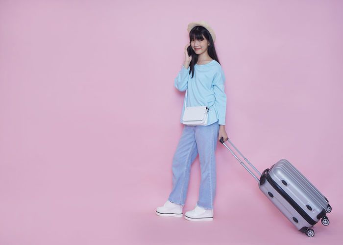 Full length portrait of woman standing against pink background
