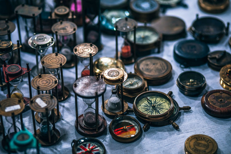 High angle view of navigational compasses and hourglass at market stall