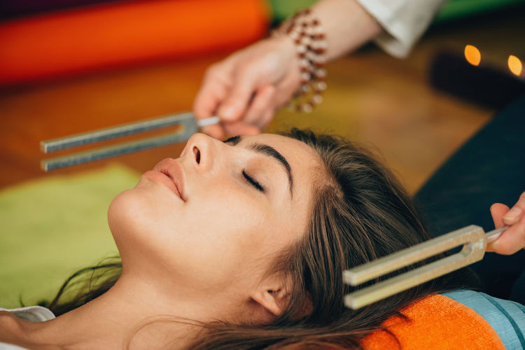 Cropped Hands Of Therapist Holding Equipment By Young Woman At Spa