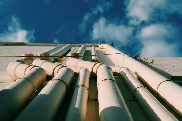 Directly below shot of pipes on building against cloudy sky