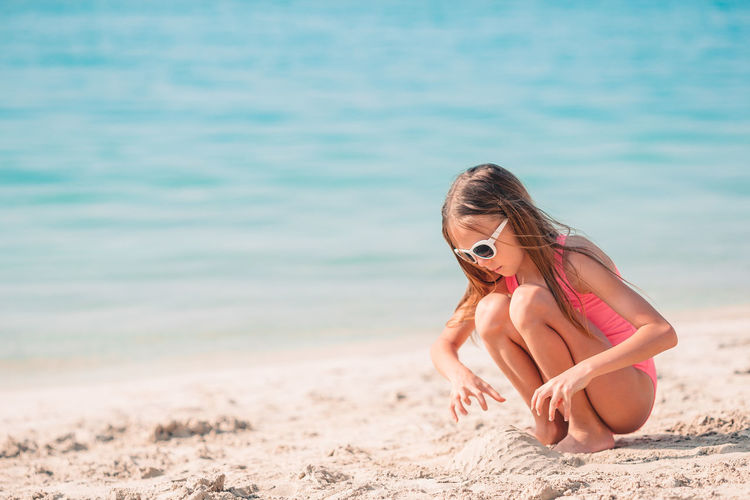 Midsection of woman at beach against sea