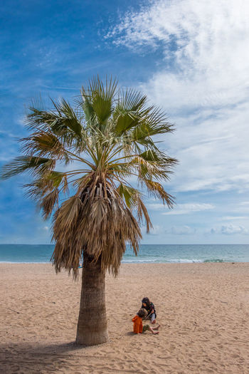 Kids Beach Beauty In Nature Cloud - Sky Coconut Palm Tree Horizon Horizon Over Water Land Leisure Activity Nature One Person Outdoors Palm Tree Plant Real People Sand Scenics - Nature Sea Sky Tree Tropical Climate Two People Water
