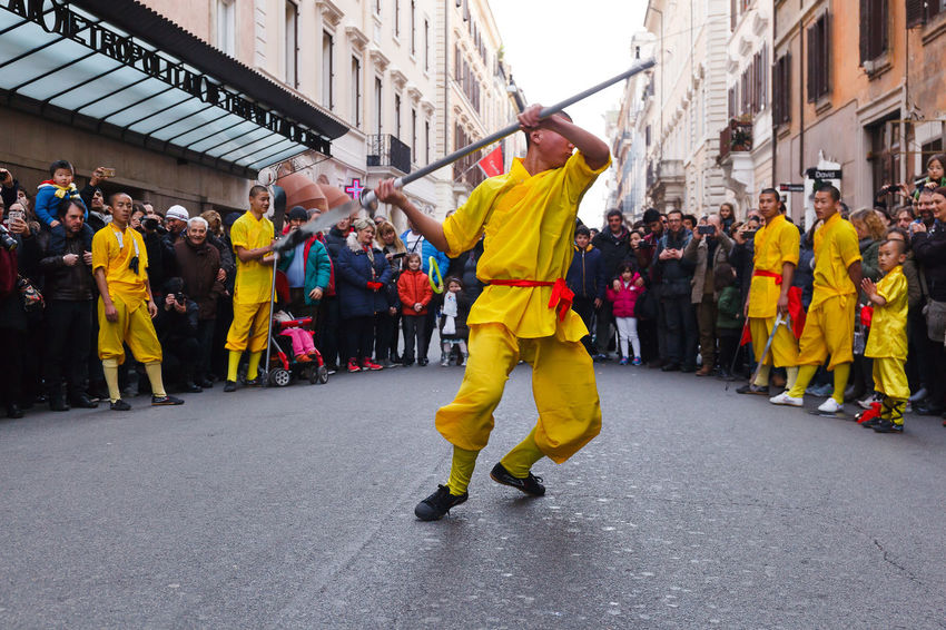 Rome, Italy - January 28, 2017: Celebration of the Chinese New Year in Rome, the year of the rooster. monk athlete in martial arts, he performs with the sword in the street during the procession. Adult Adults Only Celebration City Day Exibition Martial Arts Men Monk  Outdoors Parade People Street Yellow Color