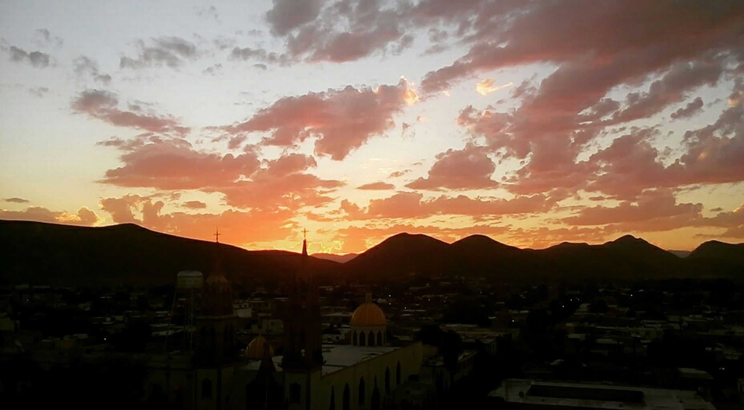 sunset, mountain, building exterior, architecture, built structure, sky, mountain range, cityscape, orange color, city, residential structure, cloud - sky, town, residential district, house, residential building, townscape, silhouette, high angle view, scenics