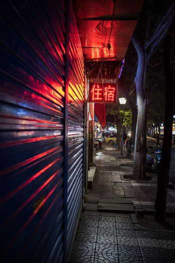 Illuminated footpath by building in city at night