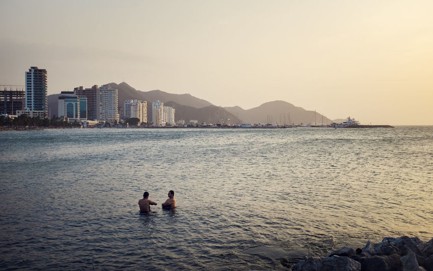 Two men swimming at sunset with the city and mountains at the horizon Beach City High Rise Horizon Over Water Mountain Sea Sky Sunset Swimming Tourism Travel Destinations Two People Water