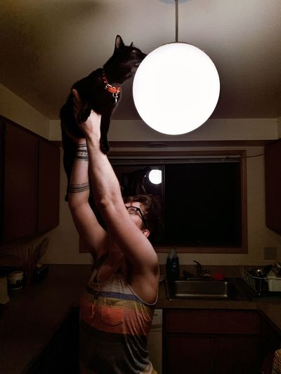 Woman holding cat by illuminated lighting equipment in kitchen at home