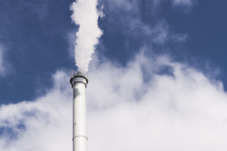 Low Angle View Of Smoke Stack Emitting Pollution In Sky