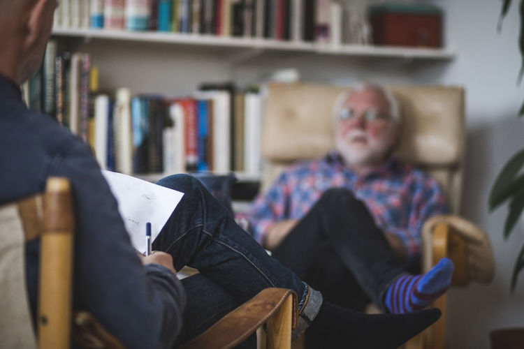 Men sitting on book at home