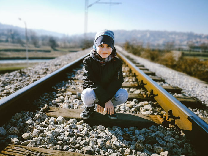 Portrait of boy crouching on railroad track