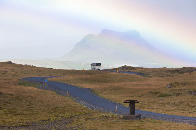South Icelandic landscape with rainbow Asphalt Beauty In Nature Bus Day Field Focus On Foreground Fog Grass Iceland Landscape Mountain Mountain Range Mountain Road Nature No People Non-urban Scene Outdoors Rainbow Road Scenics Sky Sunlight Tranquil Scene Tranquility Transportation