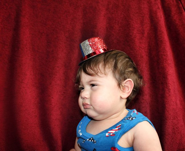 Close-Up Of Cute Baby Boy Wearing Hat Looking Away While Sitting Against Red Curtain