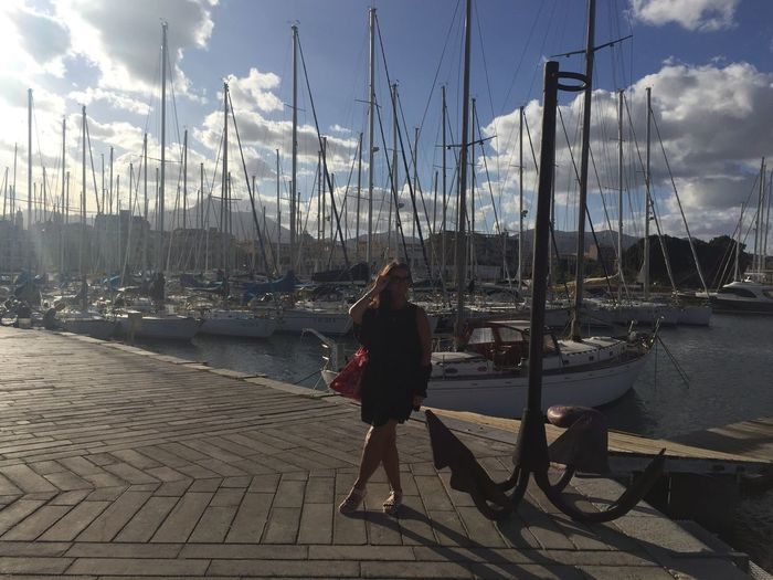 Full length of woman standing by anchor on pier against boats moored at harbor