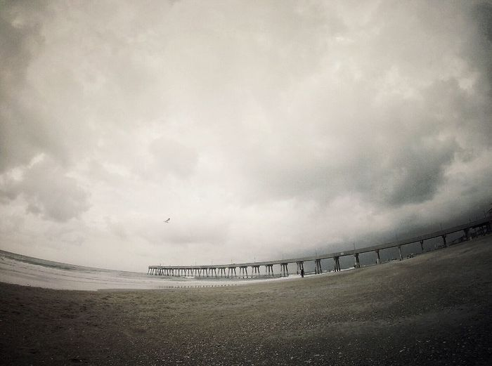 Fish-eye lens of pier over sea against cloudy sky