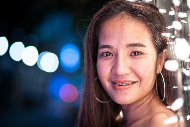 Close-up portrait of smiling young woman by illuminated string lights at night
