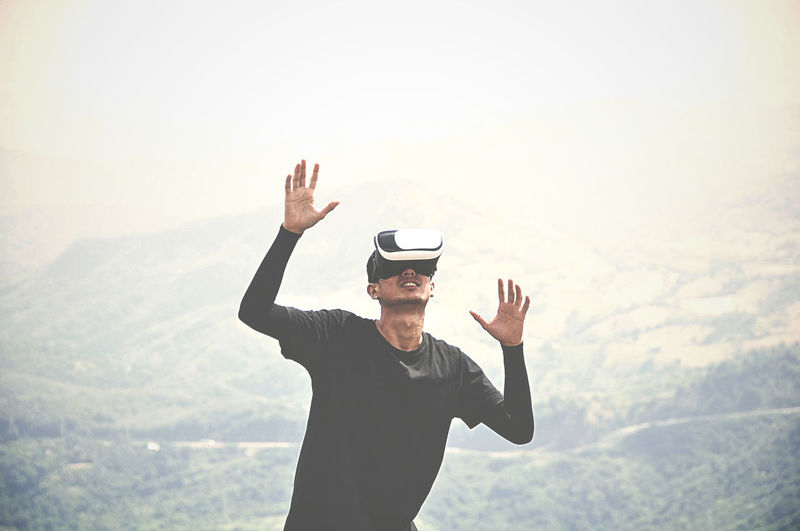 Man wearing virtual reality simulator on mountain