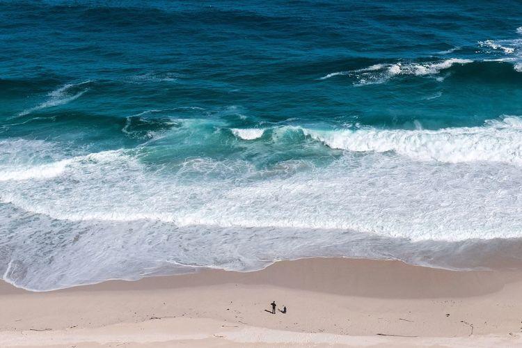 High angle view of sunny beach against ocean