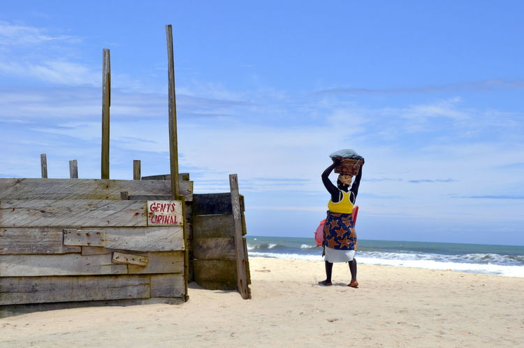 An african woman carrying a bowl on her head Beach Blue Carrying A Bowl On The Head Folkways Ghana Ghanaian Person Poor  Poverty Sky Sun Traditional Traditional Clothes Urinal Walking Woman