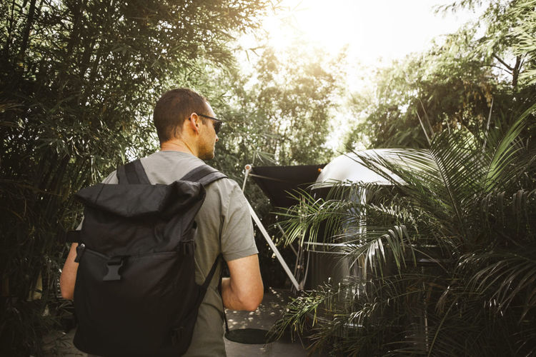 Rear view of man standing by plants against trees