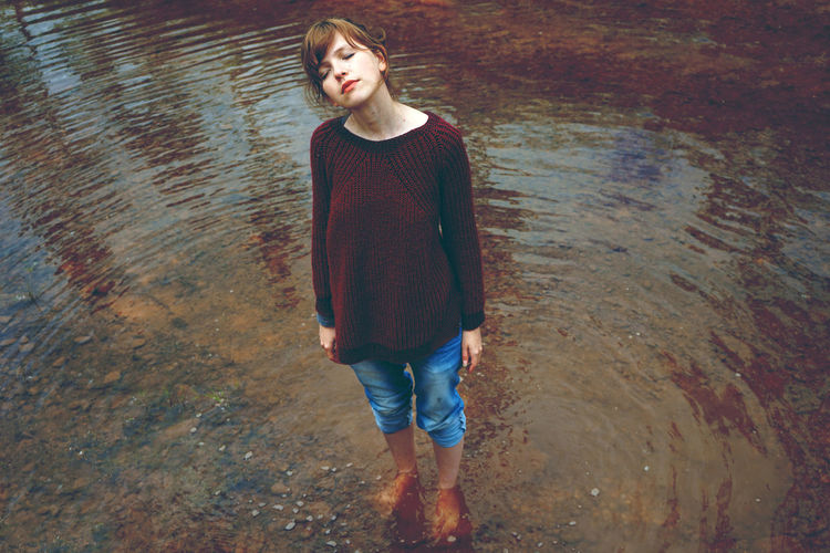 Ankle Deep In Water Casual Clothing Contemplation Day Front View Full Length High Angle View Jeans Leisure Activity Lifestyles Looking Nature One Person Outdoors Real People Rippled Standing Water Young Adult