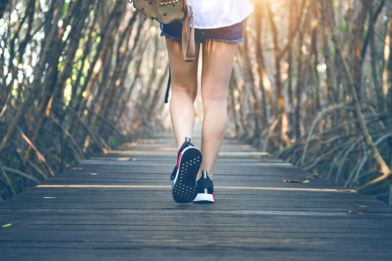 Low section of woman running on boardwalk