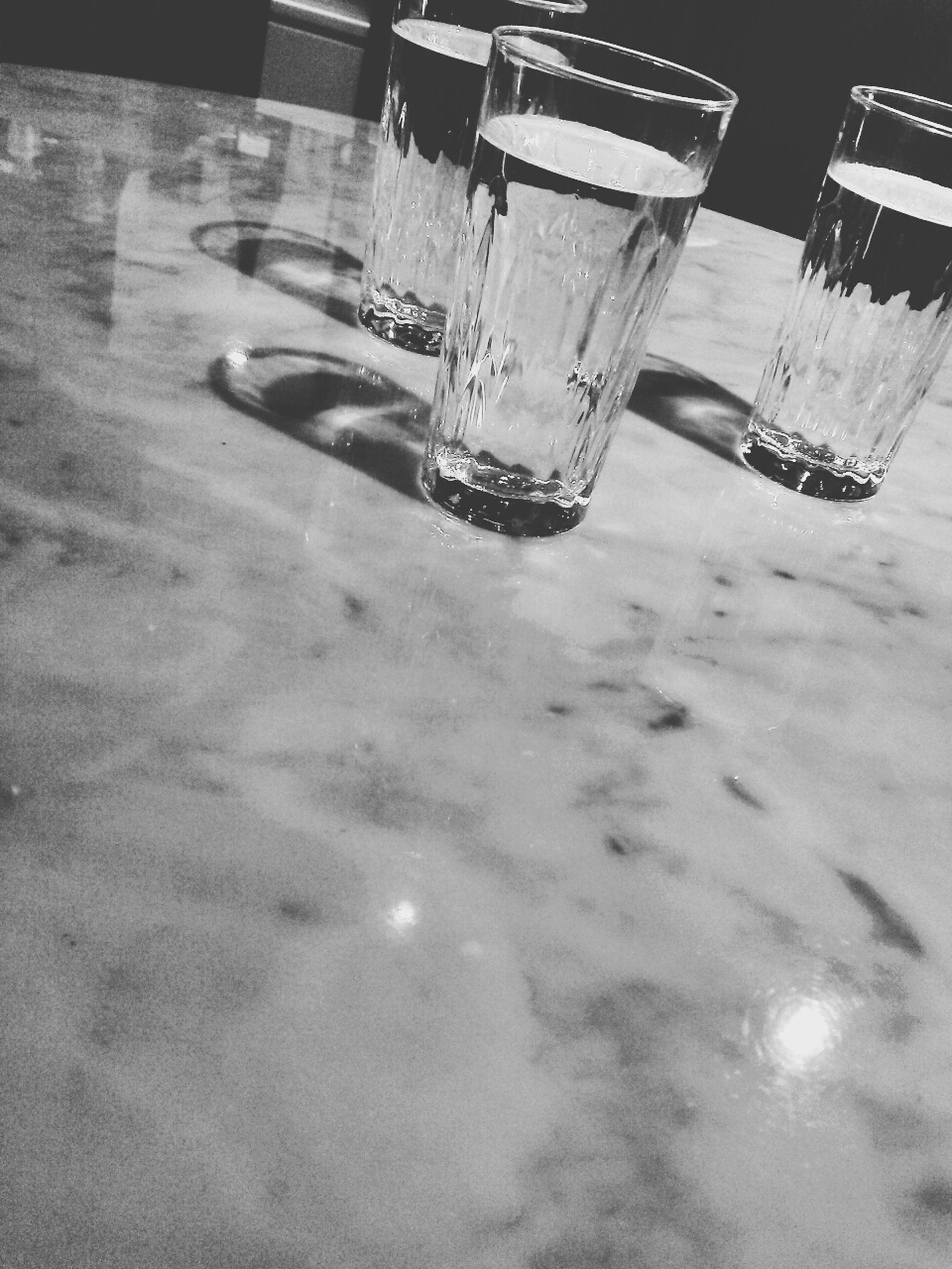 reflection, mode of transport, water, transportation, table, glass - material, drinking glass, sunlight, drink, refreshment, transparent, day, car, no people, high angle view, indoors, shadow, nautical vessel, land vehicle