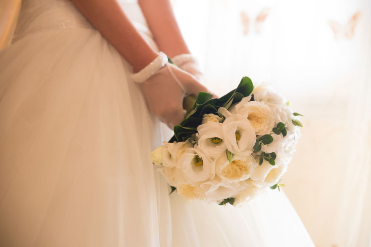 Midsection of bride wearing wedding dress while holding bouquet
