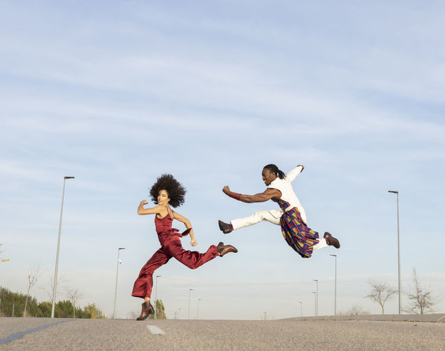 Full length of woman jumping against the sky