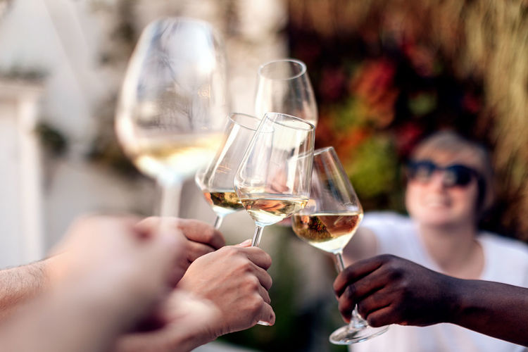 Toast with white wine. people clinking glasses with wine on terrace, cafe, restaurant, party.