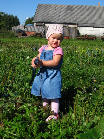 Watwring the garden Barn Assistant Boys Building Casual Clothing Child Childhood Front View Full Length Granddaughter Grassland Grasslevelseries Hat Innocence Looking At Camera Men Nature Offspring One Person Outdoors Plant Portrait Stall Standing Watering The Garden