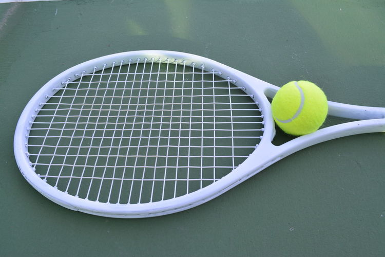 High angle view of ball and tennis racket at sports court