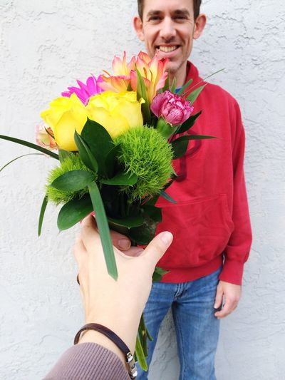 Cropped image of woman receiving bouquet from boyfriend against wall