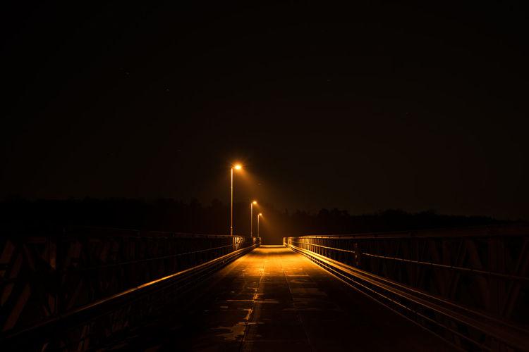 Illuminated empty bridge against sky at night