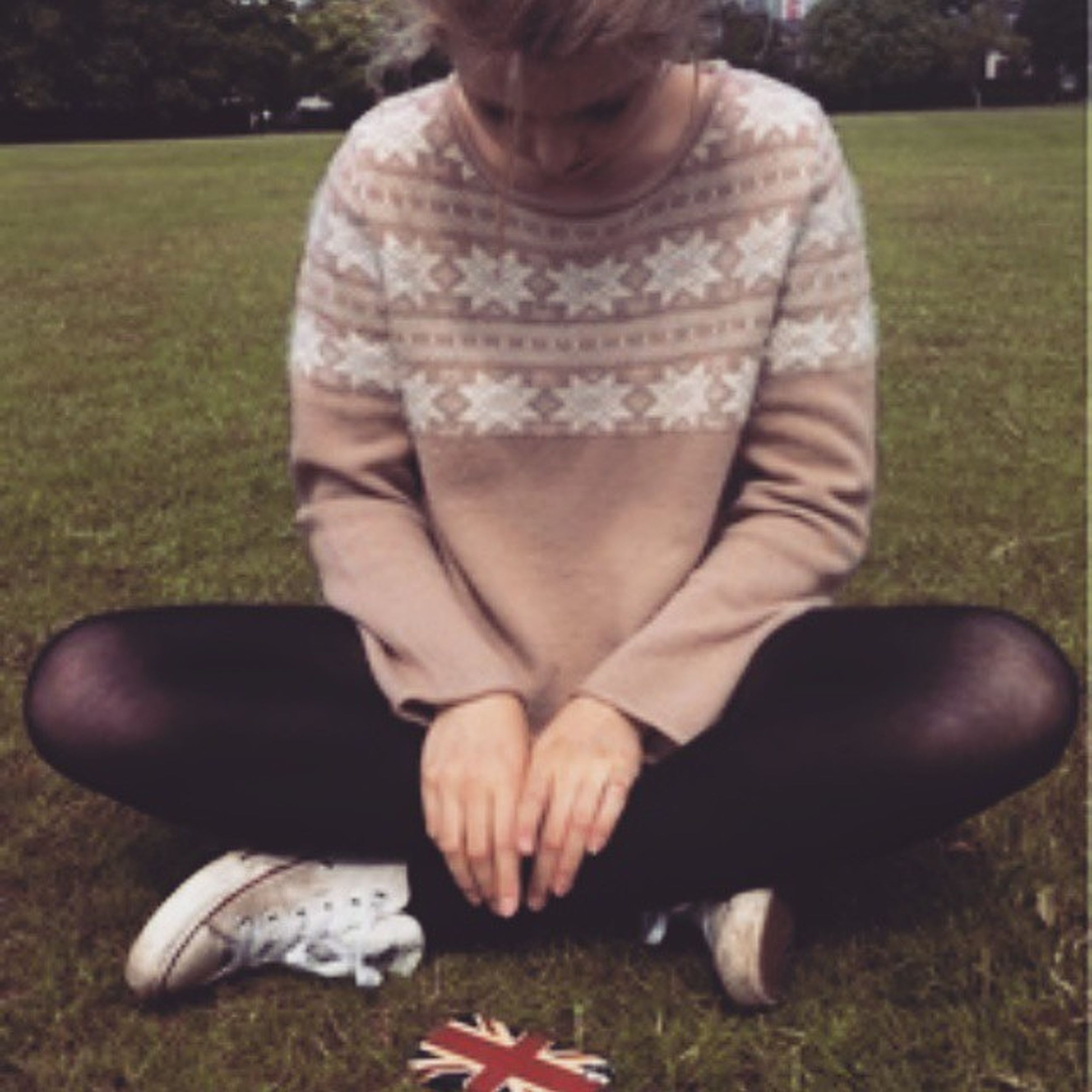 lifestyles, grass, leisure activity, low section, childhood, field, casual clothing, park - man made space, focus on foreground, person, grassy, outdoors, relaxation, sitting, day, elementary age, full length