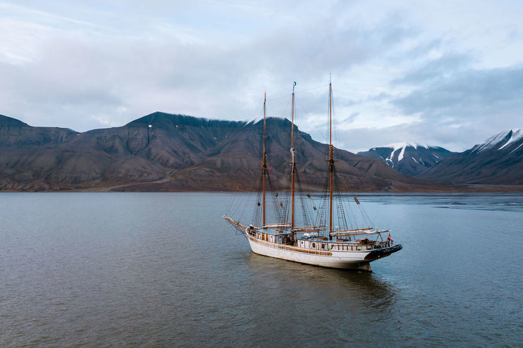 Mountain Water Nautical Vessel Cloud - Sky Transportation Mode Of Transportation Sky Waterfront Scenics - Nature Mountain Range Sea Beauty In Nature Tranquil Scene Nature Tranquility Sailboat Day Non-urban Scene No People Outdoors Yacht Anchored