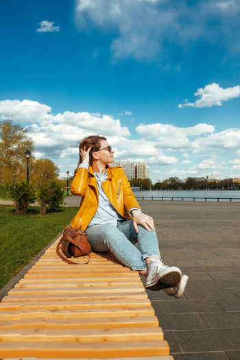 Young woman looking away while sitting against sky