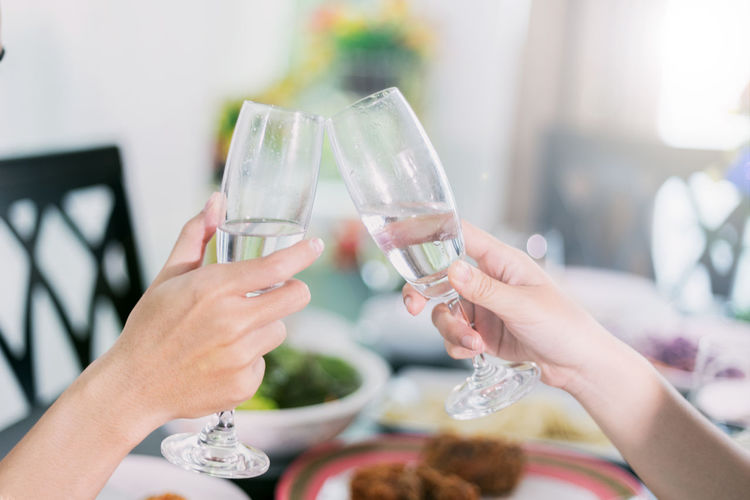 Cropped Hands Of Female Friends Toasting Champagne Flutes At Dining Table