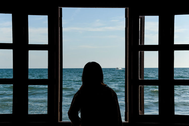 Rear view of silhouette man standing by sea against sky seen through window