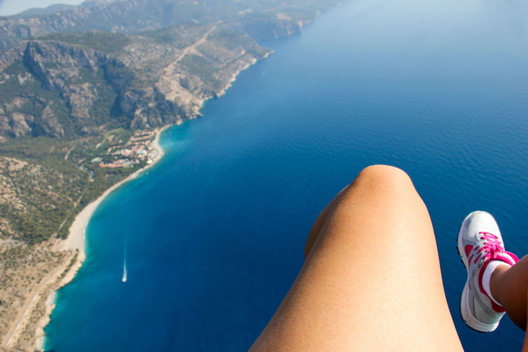 Low section of woman paragliding over sea