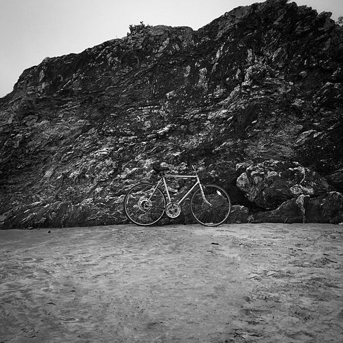 Bicycle on rock by mountain against sky