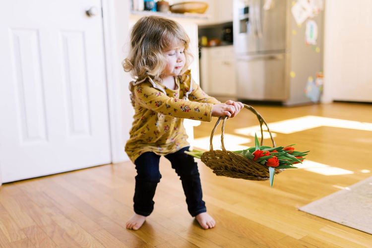 Full length of cute girl holding hardwood floor at home