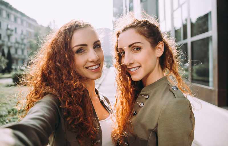 Portrait of smiling siblings on footpath in city
